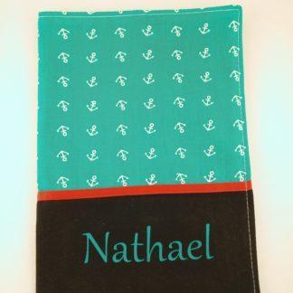 Protège carnet de santé vu de face avec tissu ancres blanches sur fond turquoise, liseré rouge et prénom turquoise sur fond noir