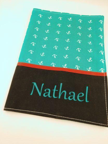 Protège carnet de santé vu de 3/4 avec tissu ancres blanches sur fond turquoise et, liseré rouge et prénom turquoise sur fond noir