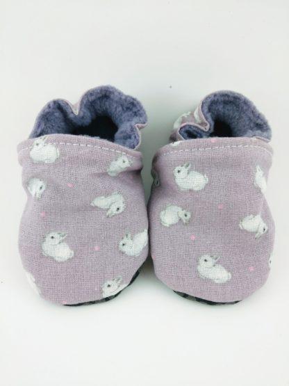 Paire de chaussons souples bébés en tissu mauve avec des petits lapins blancs