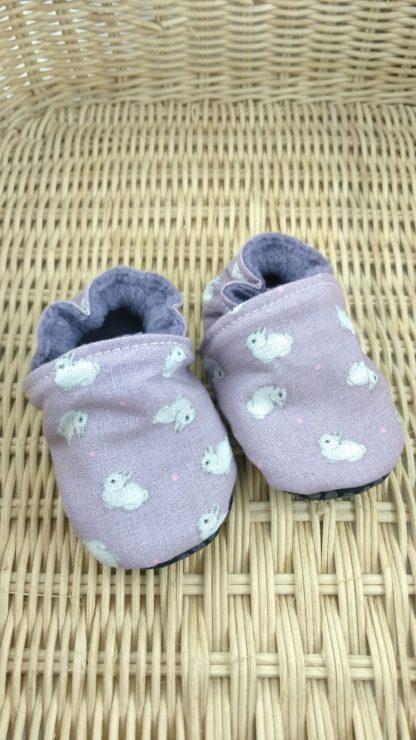 Paire de chaussons souples bébés en tissu mauve avec des petits lapins blancs sur un panier