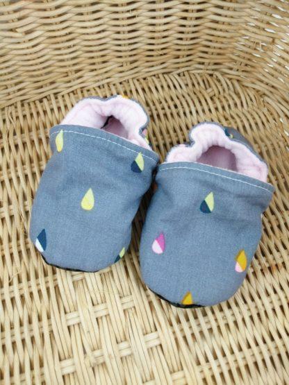 Paire de chaussons souples bébé en tissu gris avec de petites gouttes bicolores posés sur un panier