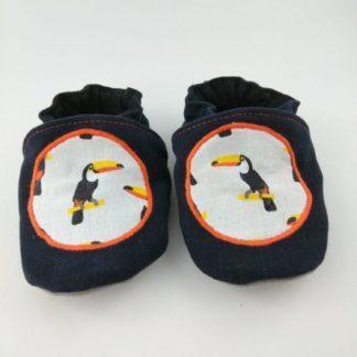 Paire de chaussons souples bébé avec motif toucan et liseré orange