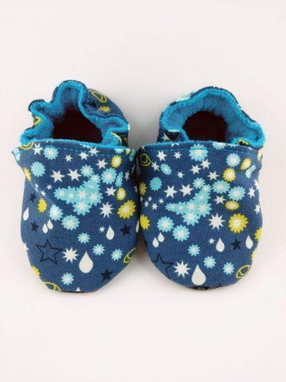 vue de face de la paire de chaussons souples bébé avec étoiles et gouttes sur fond bleu foncé