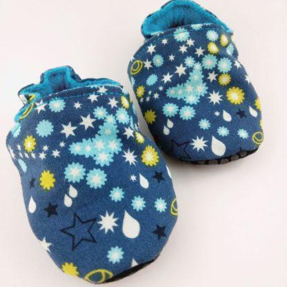 paire de chaussons souples bébé avec étoiles et gouttes sur fond bleu foncé